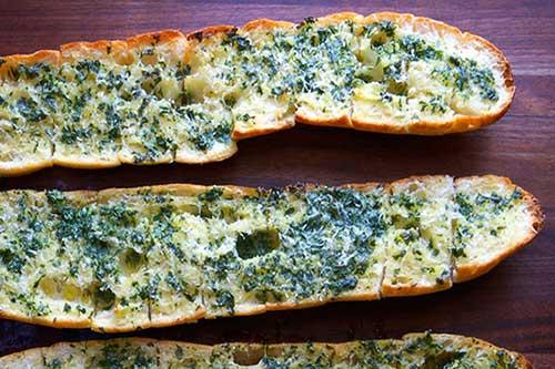 سه عدد نان باگت از وسط برش خورده و آغشته به کره و سبزی و در فر پخته شده