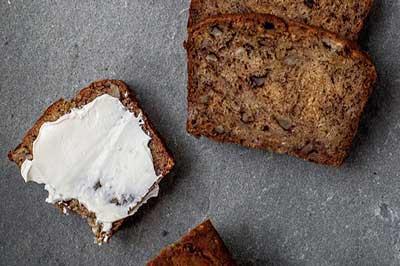 چند برش نان موز قهوهای رنگ که رو ی سطحی خاکستری رنگ قرار داده شدهاند و روی یکی از انها خامه مالیده شده است