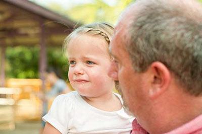 دختر خردسال زیبا با موهای طلایی در حال گریه کردن در آغوش یک مرد میانسال