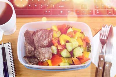 یک بشقاب پر از گوشت و سبزیجات روی یک میز چوبی در کنار یک لیوان قهوه ، یک کارد . چنگال با دسته چوبی، یک دفترچه و یک خودکار و یک کیبورد