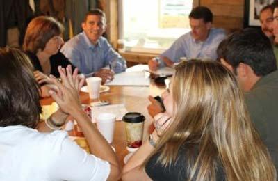 سه زن و پنج مرد دور یک میز نشسته و در حال بحث کردن هستند