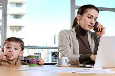 زن در کنار کودک در حال کار با لپ تاپ