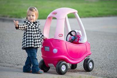 دختر خردسال زیبا در کنار ماشین اسباب بازی صورتی خود ایستاده و به سمتی اشاره میکند