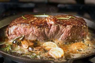 تابه چدنی حاوی یک تکه بزرگ گوشت قرمز ، چند حبه سیر و مقداری رزماری