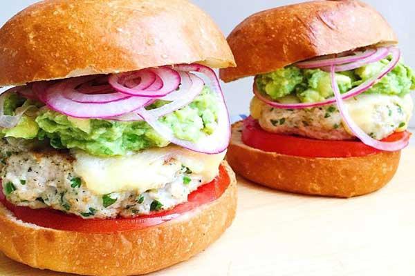 دو ساندویچ همبرگر مرغ با نان بریوش و گوآکامولی و حلقههای پیاز قرمز و گوجه