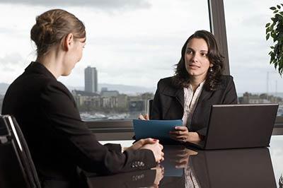 یک زن با موهای تیره و کت سیاه وپیراهن سفید و یک پرونده آبی در دست در حال حرف زدن با زنی دیگر