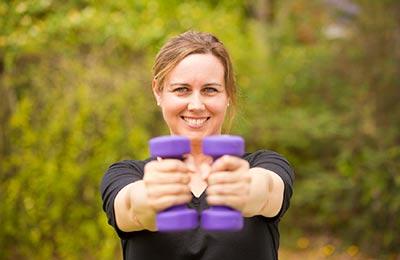 زن با لباس سورمهای در حالی که دو وزنه سبک بنفش در دست دارد دستان خود را دراز کرده ، به دوربین نگاه میکند و میخندد