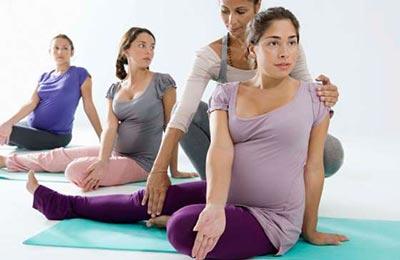 سه زن باردار در حال تمرینات یوگا در حالی که زنی دیگ به یکی از آنها آموزش میدهد