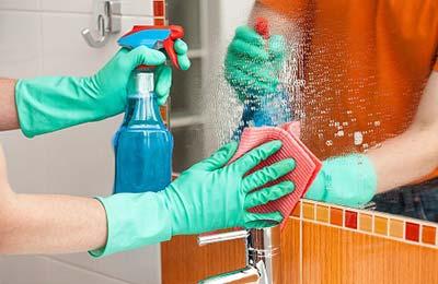 دستان یک زن با دستکش در حالی که با یکی از دستانش روی آینه اسپری کرده و با دست دیگر پاک میکند