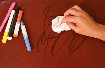 یک دست که در حال پاک کردن خطوط ماژیک از روی میز با یک دستمال سفید است