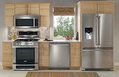 یک آشپزخانه با کابینتهای چوبی و یخچل ساید بای ساید و ماشین ظرفشویی و گاز و فر استیل