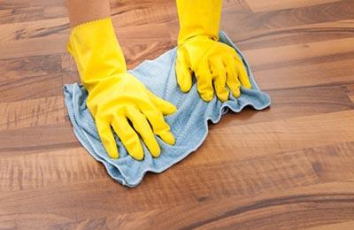 دستانی با دستکشهای زرد در حال پاک کردن پارکت با یک دستمال آبی