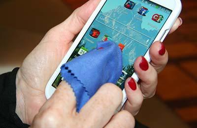 دستان یک زن با ناخنهای لاک زده در حالی که با یک دستمال آبی رنگ کوچک گوشی موبایل را پاک میکند
