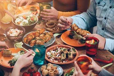 میزی پر از خوراکیهای  گوناگون و لیوانهای رنگارنگ
