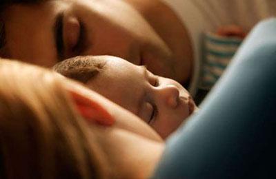 یک زن با موهای بلوند و لباس آبی و یک مرد با موهای تیره و لباس سفید و یک نوزاد بین آنها ، که خوابیدهاند
