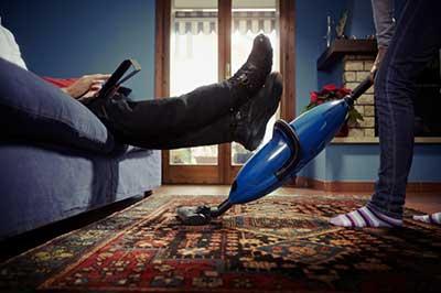 زنی با جوراب راه راه و شلوار جین در حال جارو کشیدن زیر پاهای مردی که روی کاناپه ای آبی رنگ نشسته و شلوار جین و کتانی مشکی به پا دارد