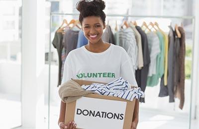 دختر سیاه پوست با موهایی خرگوشی بسته شده در حالیکه جعبه وسایل اهدایی در دست دارد