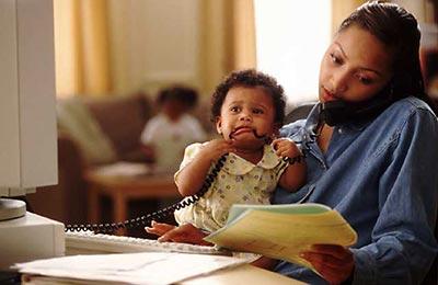 زن سیاه پوست در حال حرف زدن با تلفن در حالی که پوشهای در دست  و دختر کوچکش را در آغوش دارد و بچه در حال خوردن سیم تلفن است
