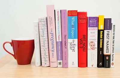چند کتاب درباره بارداری و فرزندپروری و یک لیوان دسته دار قرمز در کنارشان