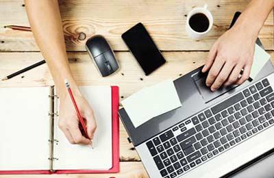 میز چوبی که برروی آن یک لپ تاپ و یک موس و یک فنجان قهوه و یک دفترچه یادداشت قرمز رنگ و دستان زنی که در حال یادداشت کردن است