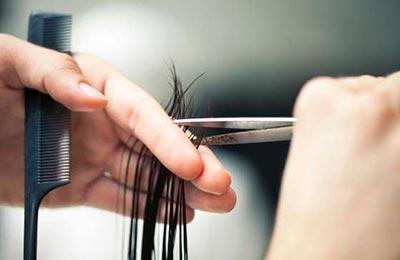 زنی در حال کوتاه کردن مو با استفاده از یک قیچی استیل و یک شانه ریز مشکی