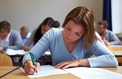 زن با لباس آبی رنگ و موهای لخت بلند در حالی که در کلاس نشسته و مشغول یادداشت برداری است