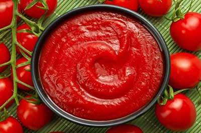 مقداری سس گوجه  داخل یک کاسه سیاه رنگ و تعدادی گوجه گیلاسی بر روی یک حصیر سبز رنگ