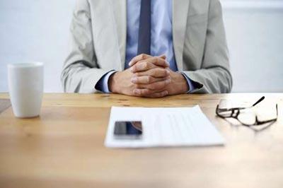 یک میز که بر روی آن یک لیوان سفید ، یک عینک، تعدادی کاغذ، یک گوشی موبایل و دستان یک مرد با کتو شلوار طوسی و پیراهن آبی قرار دارد