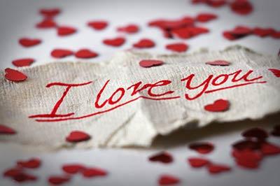 یک یادداشت عاشقانه با نوشته دوستت دارم بر روی یک تکه پارچه کرم رنگ که در اطراف آن قلبهای کاغذی کوچک پراکنده شده
